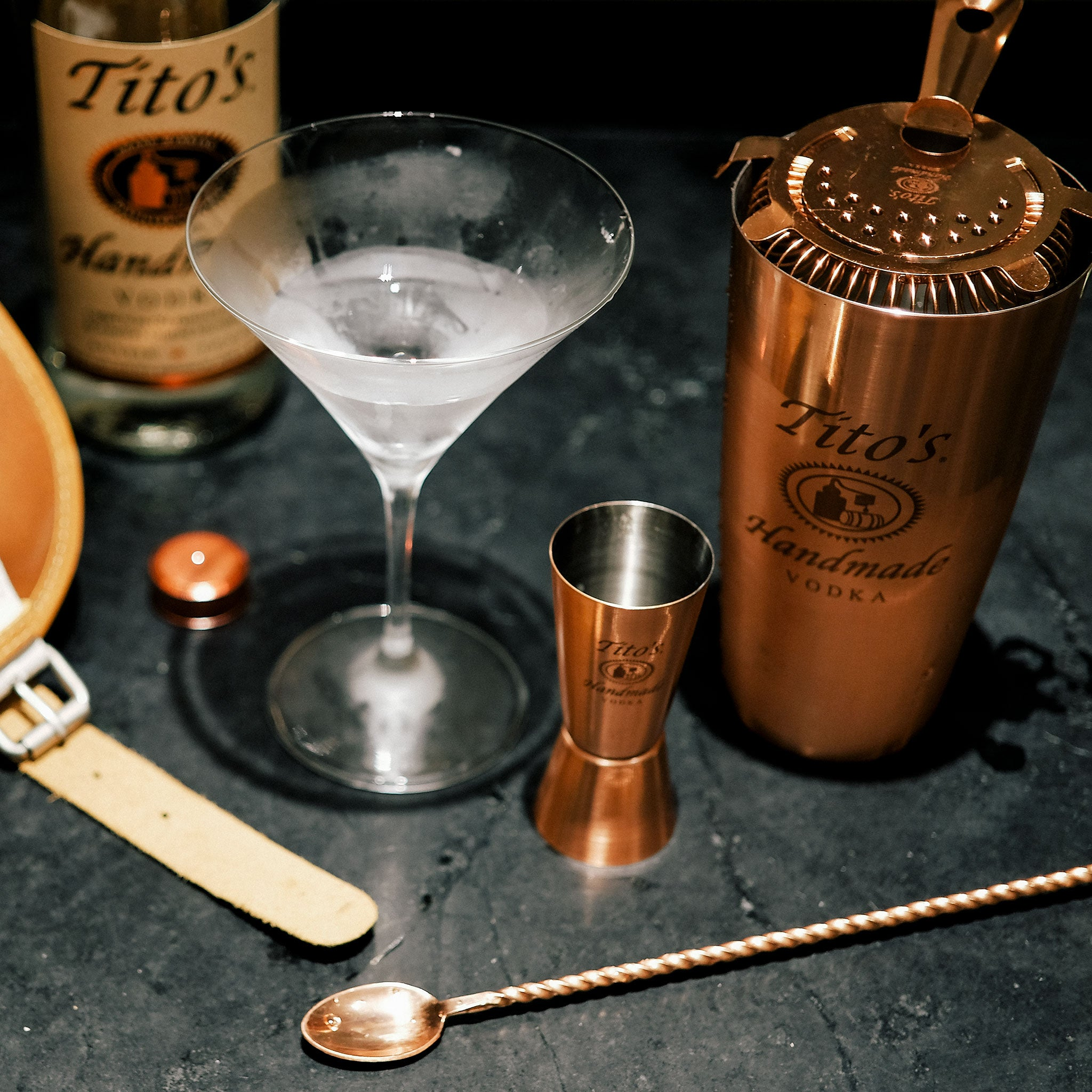 Tito's Handmade Vodka bottle with martini and copper bar tools