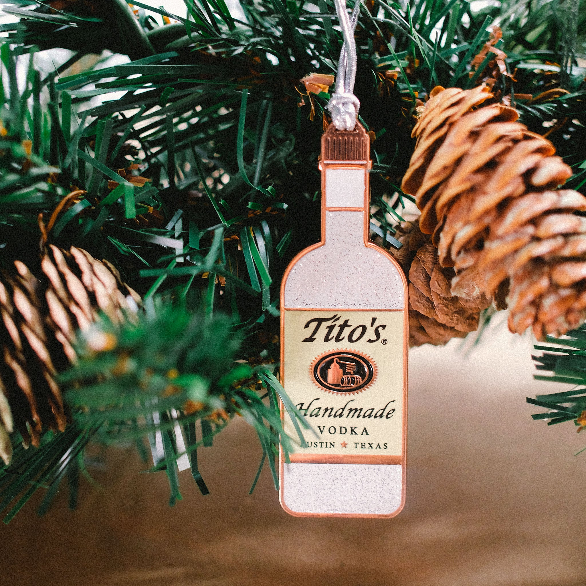 Tito's Handmade Vodka bottle ornament hanging on holiday greenery garland with pinecones