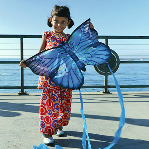 Girl holding a X Kites butterfly kite