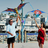 couple flying 3d dragon kite and mermaid kite ate the beach