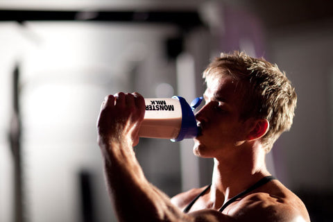 A guy drinking protein shake from his shaker.