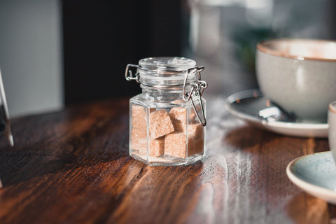 A jar full of brown sugar cubes kept on a wooden table with a cup and saucer in the background.