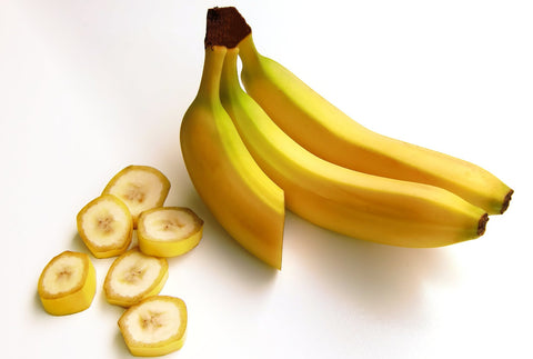 two and a half bananas kept on a white background. The other half is cut in slices.