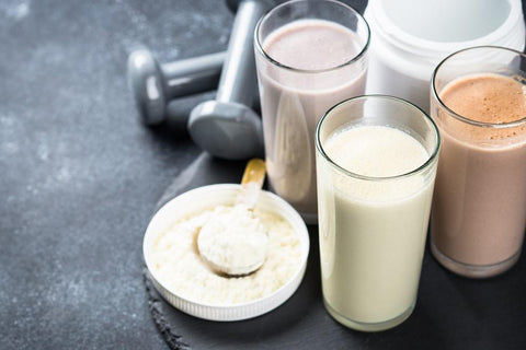 three milk shake glasses with whey protein in them and a measuring cup full of white whey concentrate.