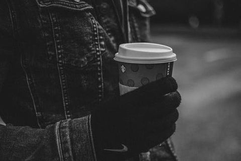 A person holding a take-away coffee cup
