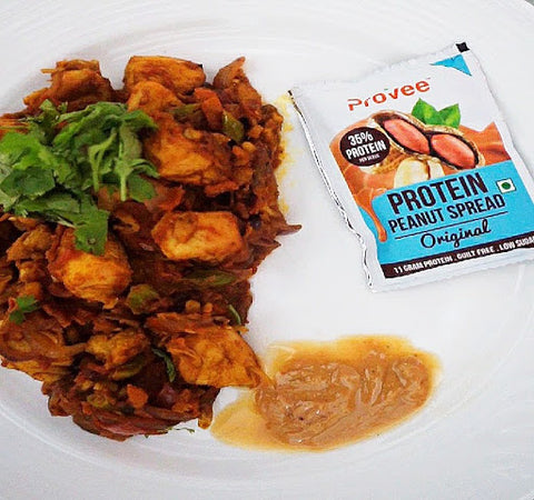 A plate with peanut butter chicken with Provee Peanut spread sachet on the side.