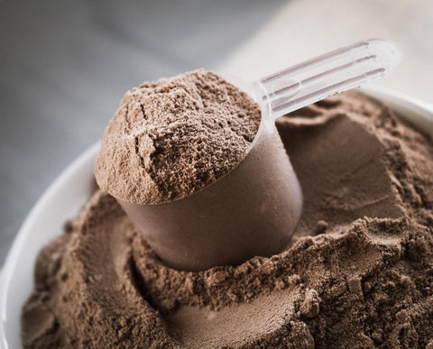A bowl full of whey powder with a measuring cup full of whey protein powder on top of it.