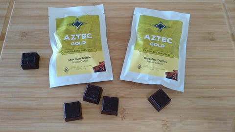Aztec Gold Hemp Cannabis Chocolate Truffle pouches on a bamboo cutting board