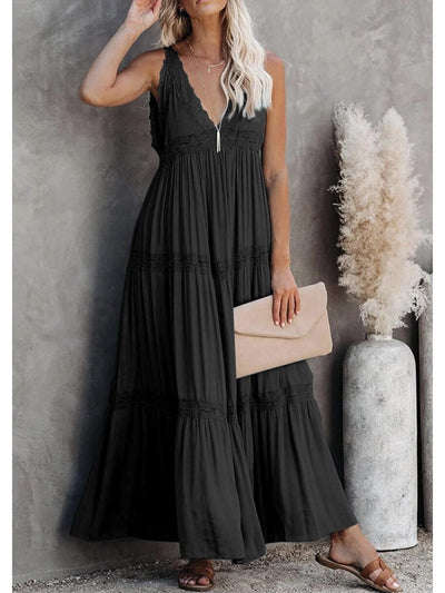 The model shows a long black dress in a casual style, sleeveless, a v-neckline and lace details accompanied by a beige clutch