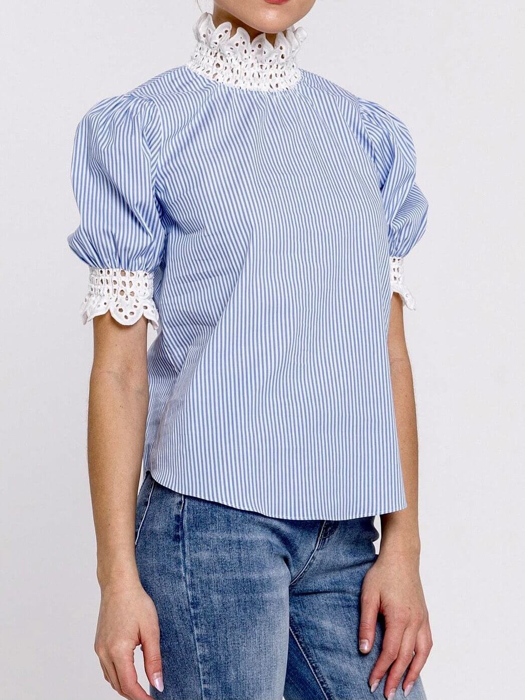 model wears top of blue and white lines, sleeves and high neck with embroidered fabric details
