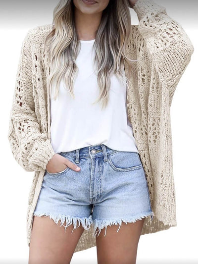 Model is wearing beige open-front knit sweater with white top and denim shorts