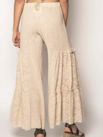 Model shows the back of boho chic bell bottom pants, beige, with tassel details