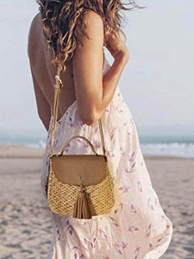 model carries on her shoulder boho bag in a casual camel color of natural fibers shell with tassel detail