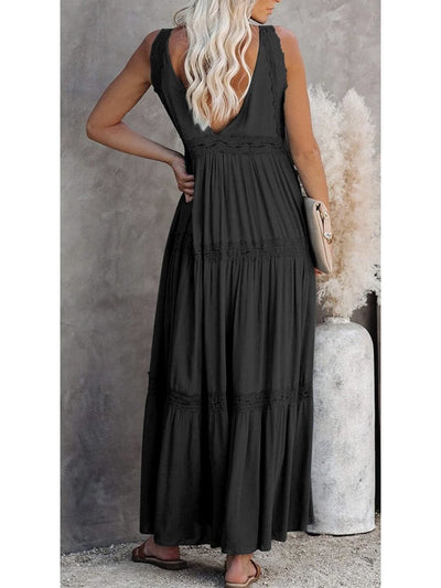 The model shows the back of a long black dress in a casual style, sleeveless, a v-neck at the back and lace details