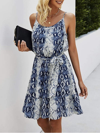 Model wears short blue snake dress, sleeveless, drawstring at the waist and round neck accompanied by a black handbag