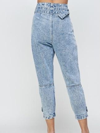 Back stand in high cut blue jogger Jeans, with belt and buckle to adjust, zip to close, front pockets and button details on the lower part of the legs.