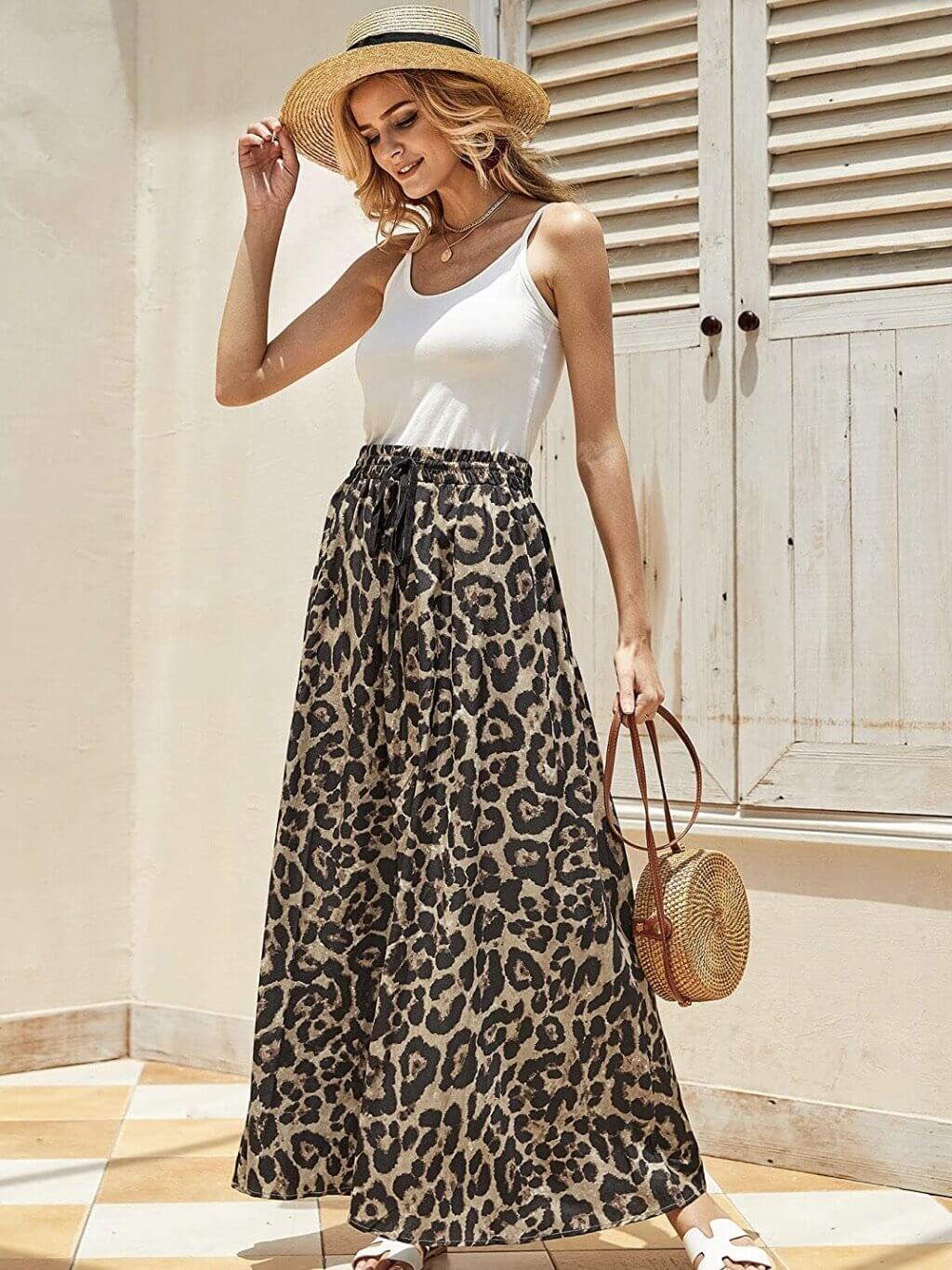 Model wears long skirt made of animal print, with elastic waist and adjustable drawstring. Combined with white top, hat and wallet.