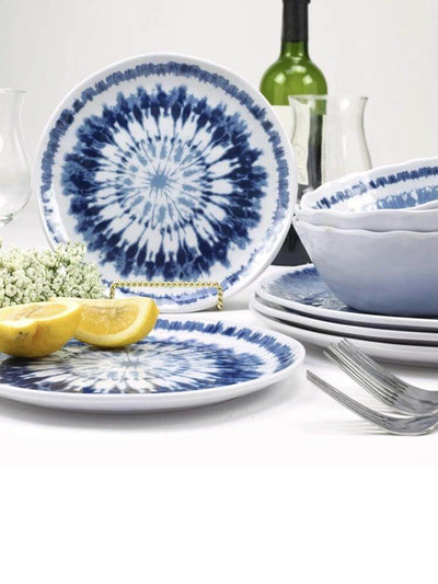 Boho blue dinnerware set accompanied by bottle of wine and fruits