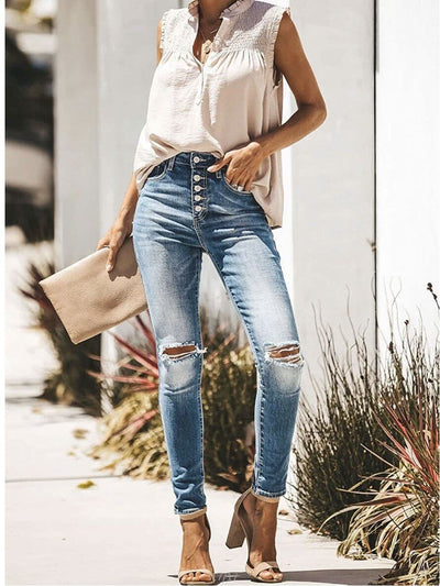 beige top, sleeveless in combination with ripped blue jeans, clutch and sandals