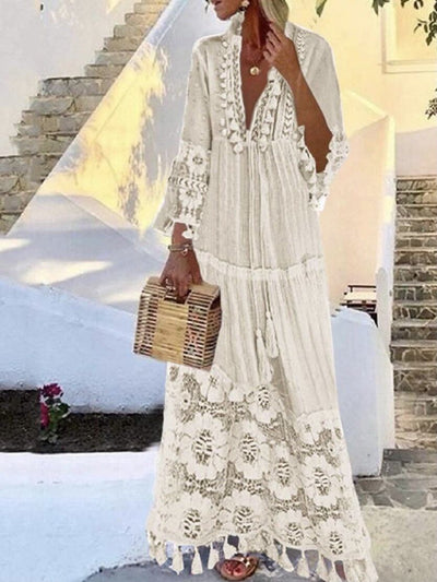 Model wears a white boho dress, mandarin collar, V-neck, long sleeves, drawstring at the front and tassel details accompanied by a boho bag