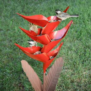 Heliconia Bird Feeder in lawn, with three birds perched