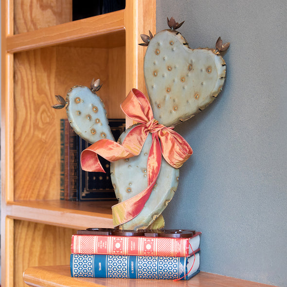 Prickly Pear Heart Sculpture with bow on shelf with books
