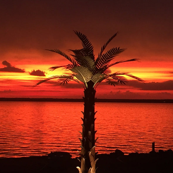 Metal Palm Tree on beach at sunset
