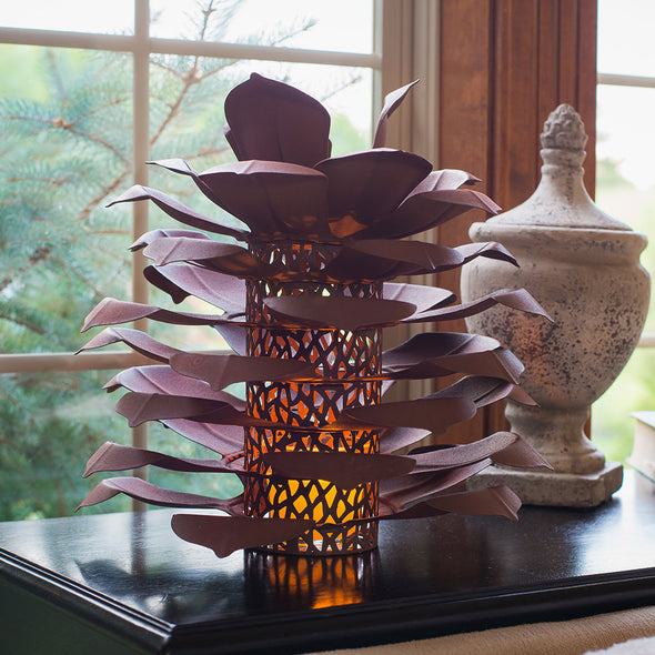 Pine Cone Luminary on end table with vase, next to window