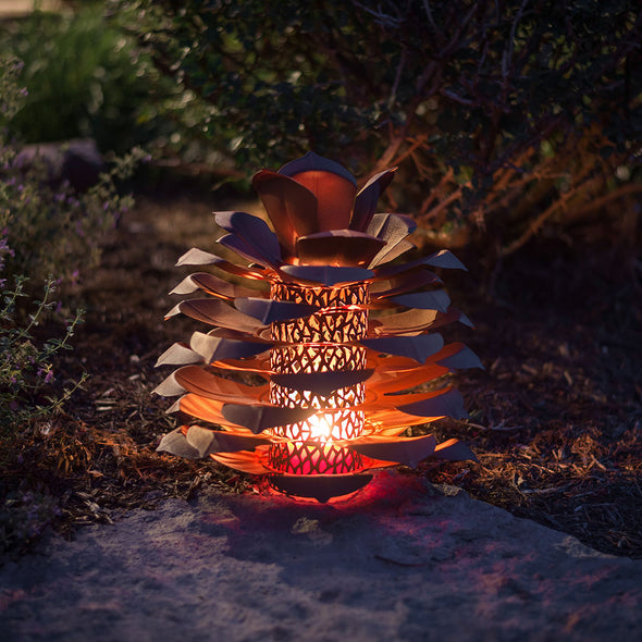 Pine Cone Luminary lit up on porch