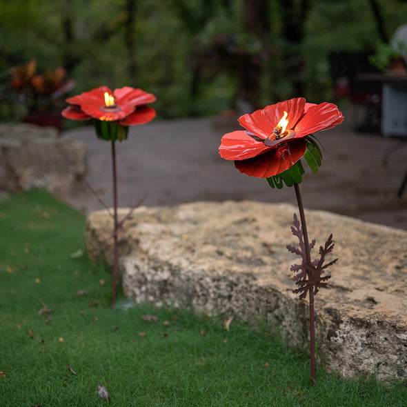 Two Red Poppy Torches in yard next to landscape stone