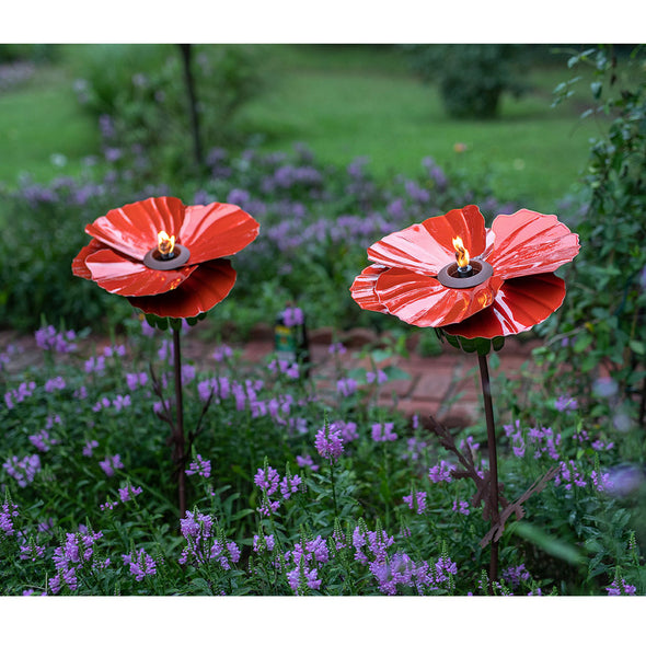 Two Red Poppy Torches in garden with flowers