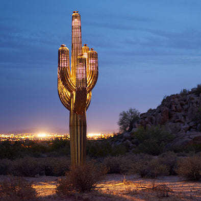 Steel Saguaro Sculpture lit up at night with cityscape in background