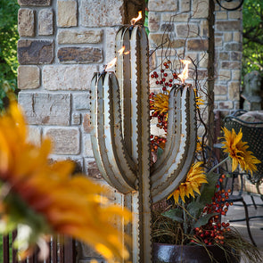 Steel Saguaro Cactus Torch with flames lit, on back porch