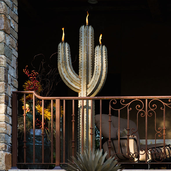 Metal Cactus Torch lit up on deck, next to railing, at night