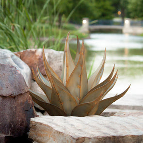 Metal agave with pond in background, next to landscape stones