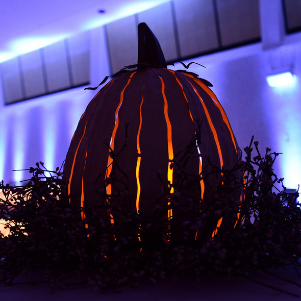 Tall Pumpkin Luminary lit up outside at night