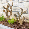 Two prickly pear sculptures in landscape bed next to home