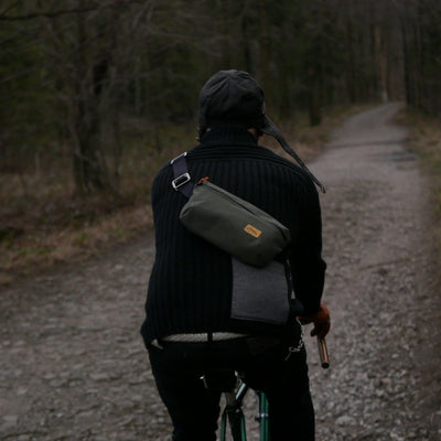 Cyclist on the forrest path wearing khaki cycling sling bag from La Jefa and sons