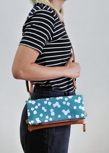 Recycled leather fold over clutch bag in teal flower on model