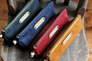 Wax canvas pencil case in red, caramel, navy and green