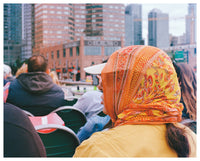 Image of woman wearing a bright orange headscarf on the ferry on the Hudson River, New York