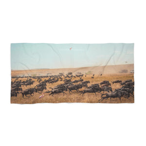 'The Wildebeest Stampede' Beach Towel