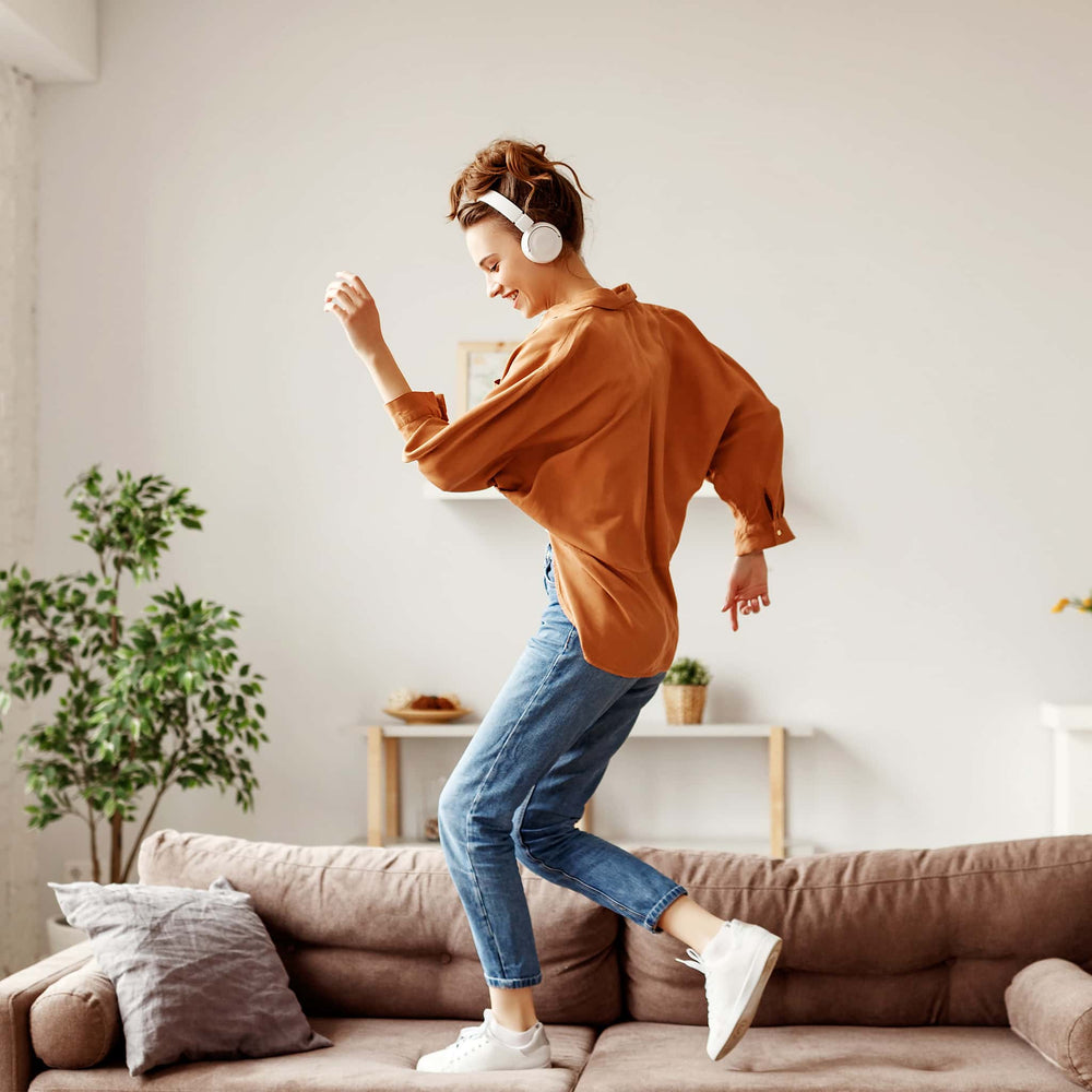Load image into Gallery viewer, Cheerful woman listening to music and dancing after using CBD oil