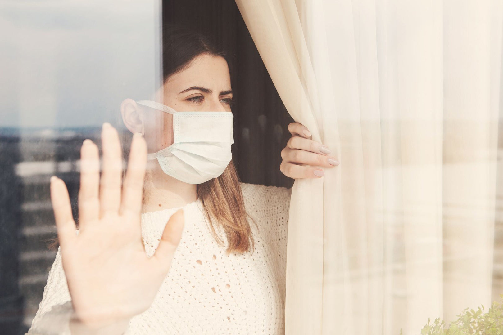 Woman with surgical mask on, looking out the window, quarantines, isolation