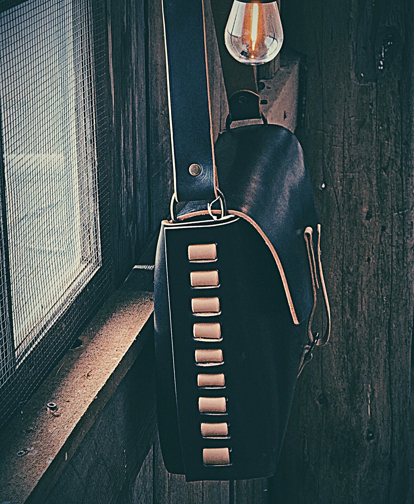 Black and Tan leather Satchel in a wooden barn