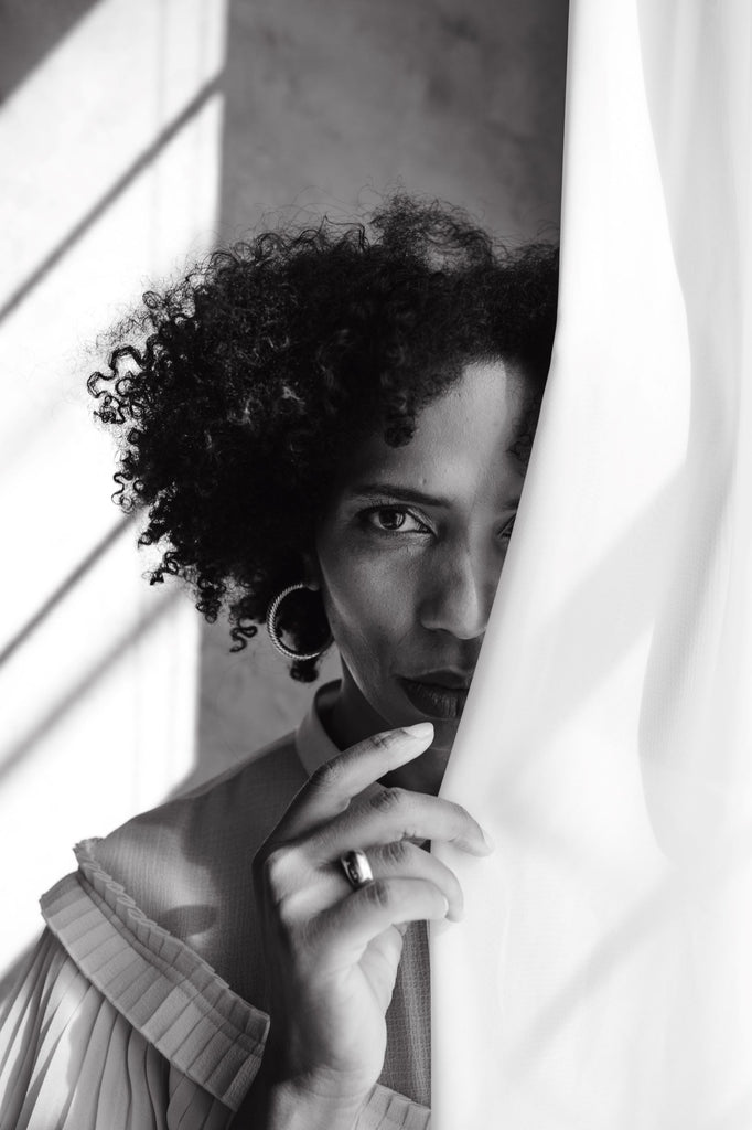 Photo of a black woman with her face half hidden by a curtain.