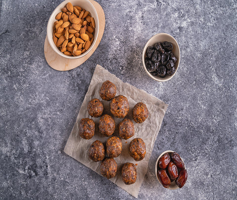 High energy balls on  plate with a side of dates and almonds.