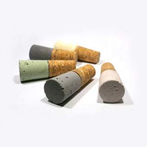 Concrete wine stoppers in pink, light grey, green, dark grey and yellow