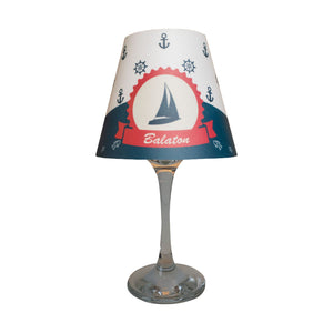 "Wine glass with white ""lamp"" shade with a blue sailing boat."