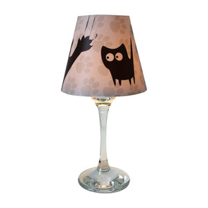 "Wine glass with white ""lamp"" shade with a black cartoon cat design and paws background."